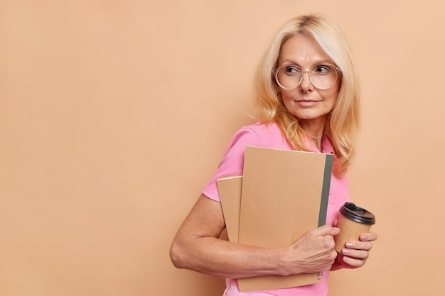 Portrait of blonde middle aged woman looks away with thoughtful expression writes checklist in notepad being deep in minds drinks aromatic takeaway coffee isolated over brown wall copy space