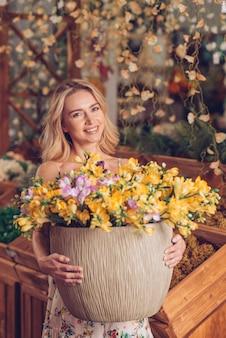 Ritratto di una giovane donna sorridente bionda che tiene grande vaso in fiori gialli