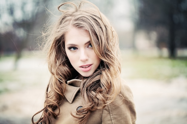 Portrait of blonde woman in a beige coat on a windy day outdoors