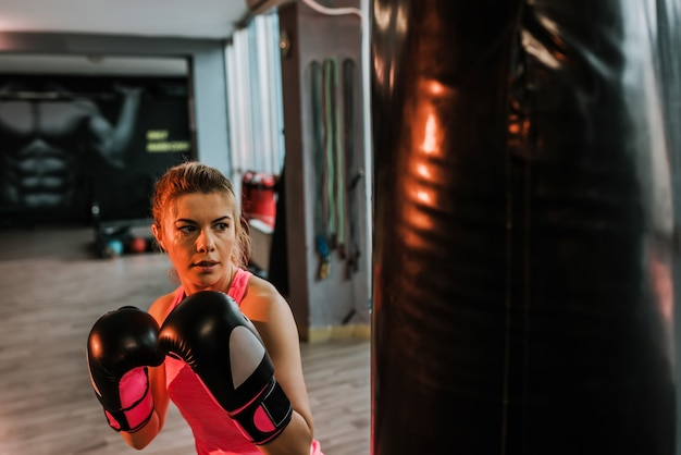 Portrait of blonde woman boxer who is training in gym.