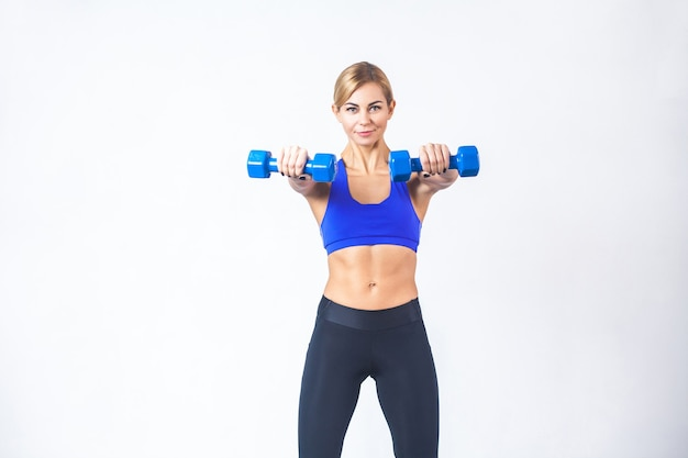 Portrait of blonde woman, demonstrate two blue dumbbells at camera. isolated on gray background, studio shot