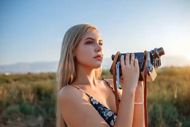 Portrait of blonde woman in floral print dress with vintage video camera in grape field during sunset