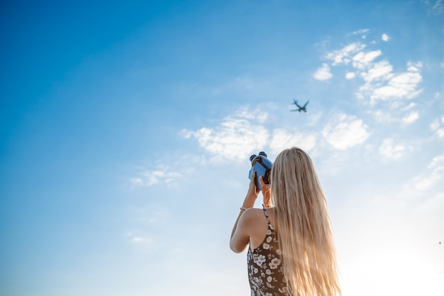 Portrait of a blonde woman in a floral print dress with a vintage video camera in a grape field records video of a plane taking off