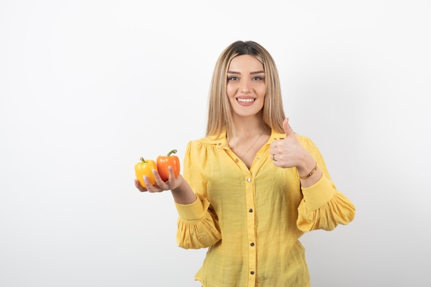 Portrait of blonde woman holding colorful bell peppers and giving thumbs up.