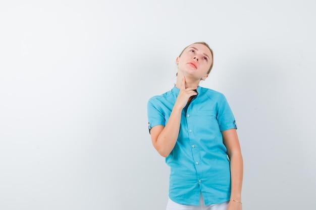 Ritratto di donna bionda che si tocca il collo isolato