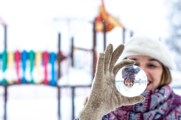 Portrait of a blonde woman wearing a beret, jacket and scarf holding in her hand a crystal ball in a snowy park.