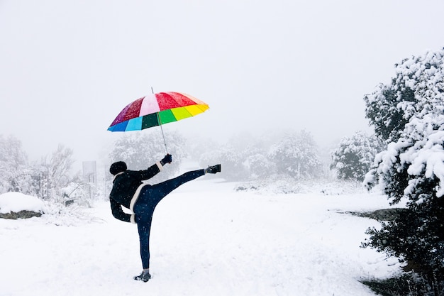 Portrait of blonde woman with colored umbrella launching a karate kick during a snowfall.