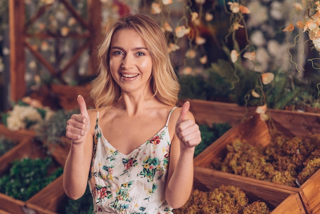 Portrait of a blonde young female florist showing thumb up sign with two hands