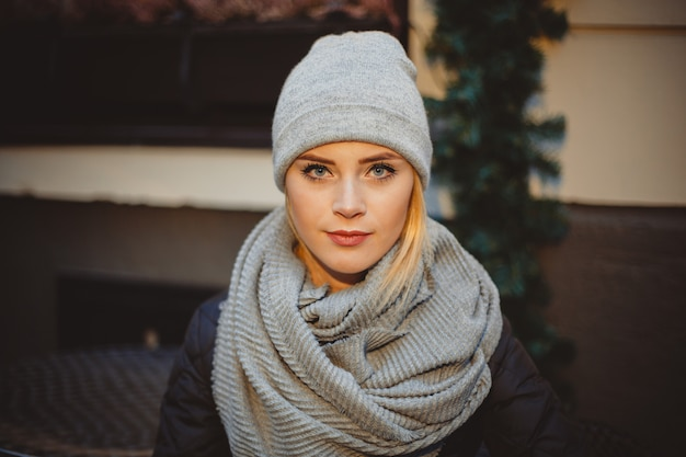 Portrait blonde young woman in black coat and scarf