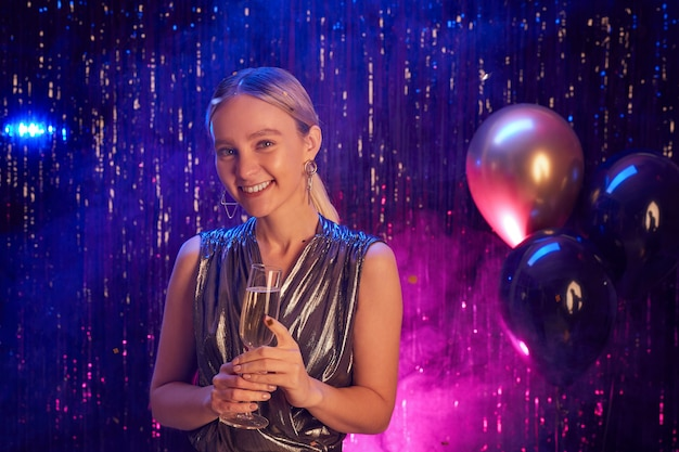 Portrait of blonde young woman holding champagne glass and smiling at camera while enjoying party in nightclub, copy space