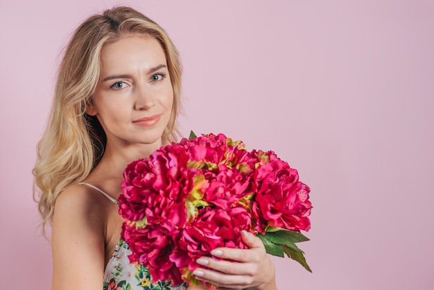 Portrait of blonde young woman holding flower bouquet in hands