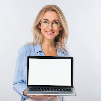 Portrait of a blonde young woman holding an open laptop with blank screen against white backdrop