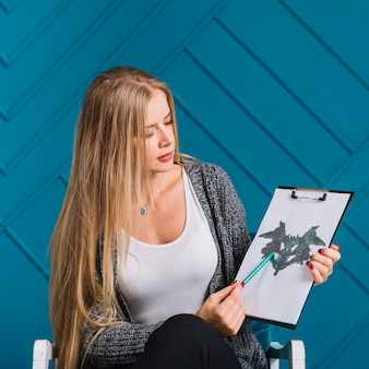 Portrait of a blonde young woman pointing pen over the rorschach inkblot test against blue wall