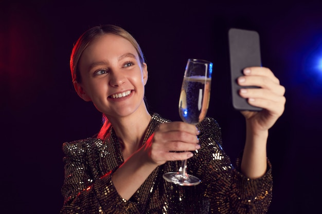 Portrait of blonde young woman taking selfie photo via smartphone while enjoying party in night club and toasting with champagne glass