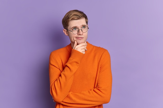Portrait of blue eyed guy ponders on something stands in thoughtful pose holds chin concentrated into distance wears casual orange jumper