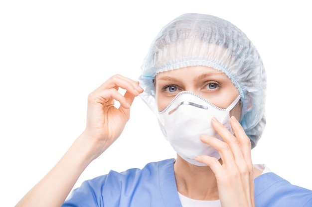Portrait of blue-eyed woman in surgical cap putting respiratory mask on face
