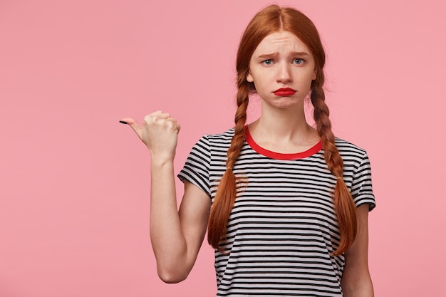 Portrait of blue-eyed young red-haired girl looks sad, upset, frustrated, pointing with thumb to the left side on blank copy space, displeased with something, lips pout, expresses insult, on pink wall