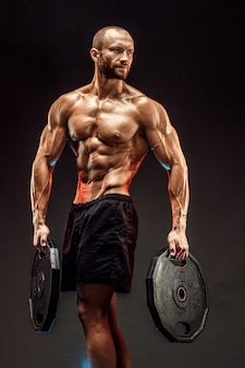 Portrait of bodybuilder with dumbbells in his arms on grey backg