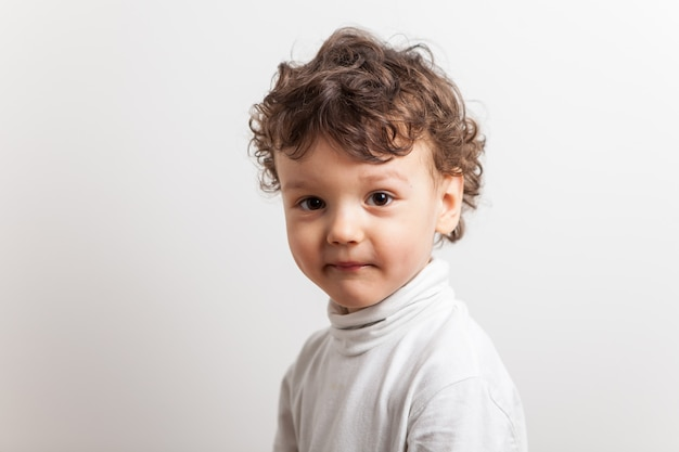 Portrait of a bold boy with curly hair of three years on a white isolated