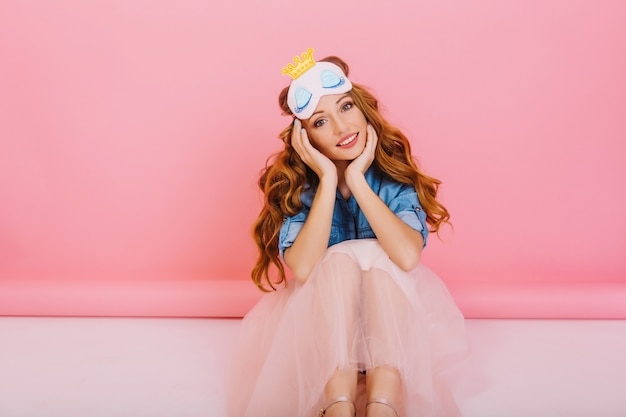 Ritratto di ragazza riccia annoiata con espressione del viso adorabile che indossa la maschera del sonno e gonna lussureggiante alla moda, isolato su sfondo rosa. adorabile giovane donna in abito elegante seduto sul pavimento nella sua stanza