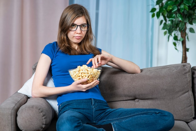 Portrait of bored girl, young single woman in glasses sitting at couch or sofa at home eating food, popcorn, watching boring tv show, movie, spending time alone at home in the evening in living room