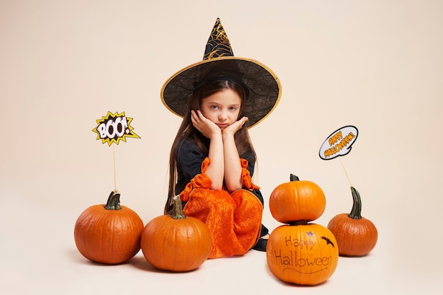 Portrait of bored little witch sitting among halloween pumpkins