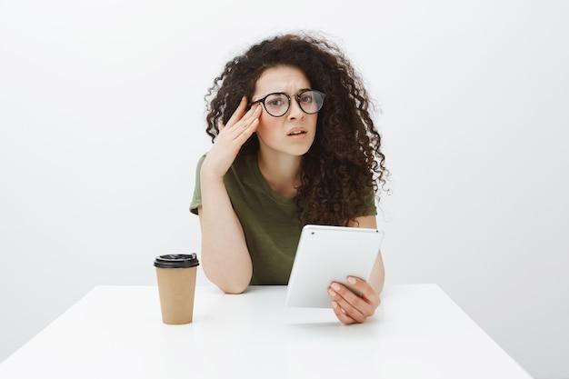 Ritratto di donna europea dai capelli ricci all'oscuro infastidita in occhiali neri, seduta a tavola, tenendo lo smartphone e bevendo caffè o tè, tenendo le mani sulle tempie