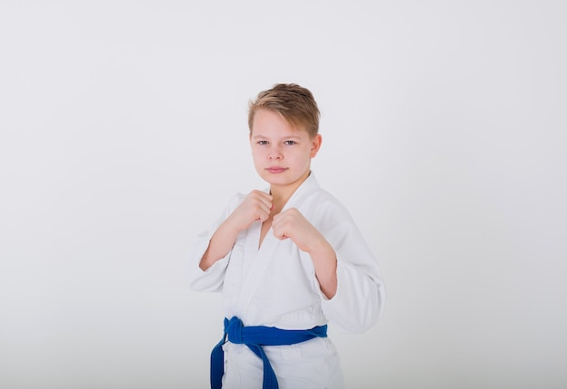 Portrait of a boy blond in a white kimono with a blue belt with hands in protection on a white wall
