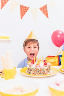 Portrait of a boy blowing candle during birthday celebration