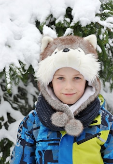 Portrait of a boy in a cap in the form of a dog on the snowy winter forest