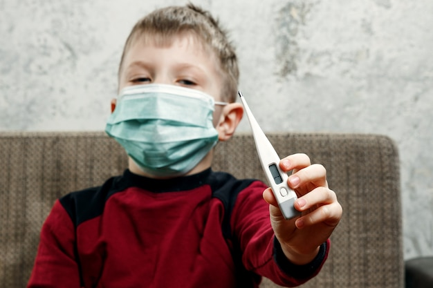 Portrait of a boy, a child in a medical mask is holding a thermometer in his hands