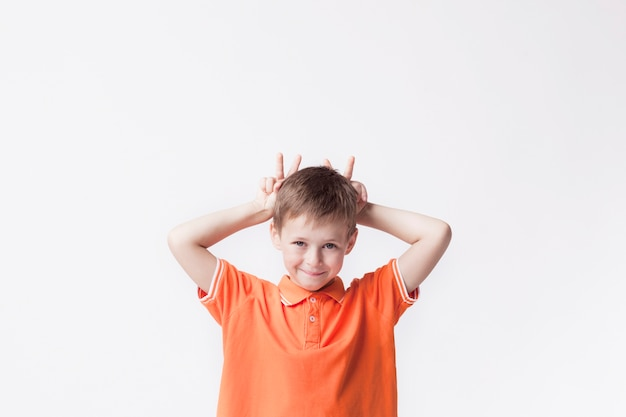 Portrait of boy child showing finger behind his head and teasing against white background