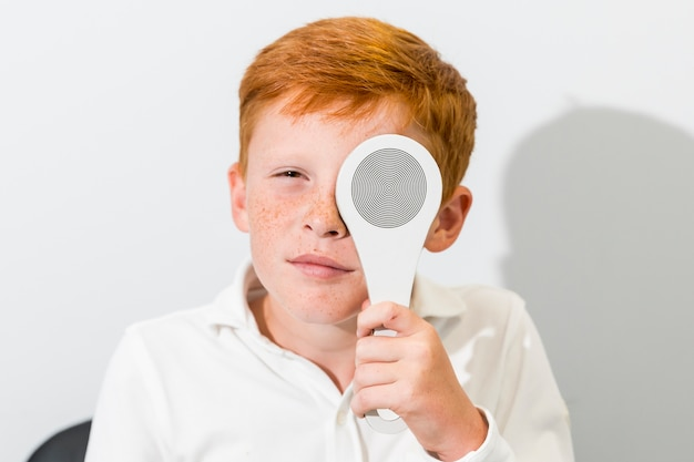 Portrait of boy covered eye with occluder in optics clinic