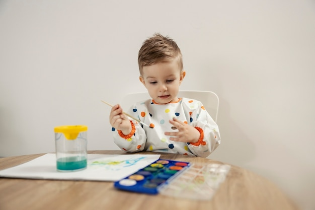 Portrait of a boy drawing with watercolors. a cute male toddler dressed in colorful polka dots sits at a table indoors and draws with a brush on paper. childhood and the development of creativity