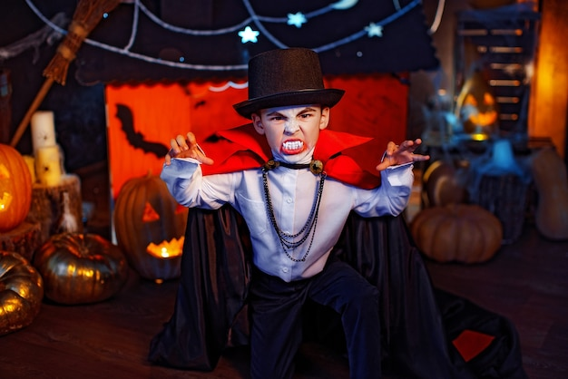 Portrait of a boy dressed in a costume of a vampire and hat over grunge background. halloween party.