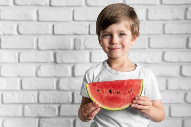 Portrait boy eating watermelon