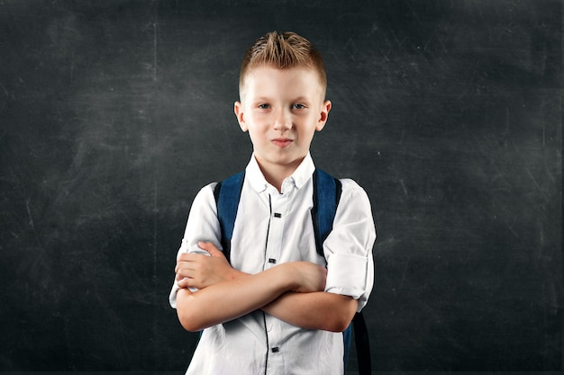 Portrait of a boy from an elementary school on a background of a school board