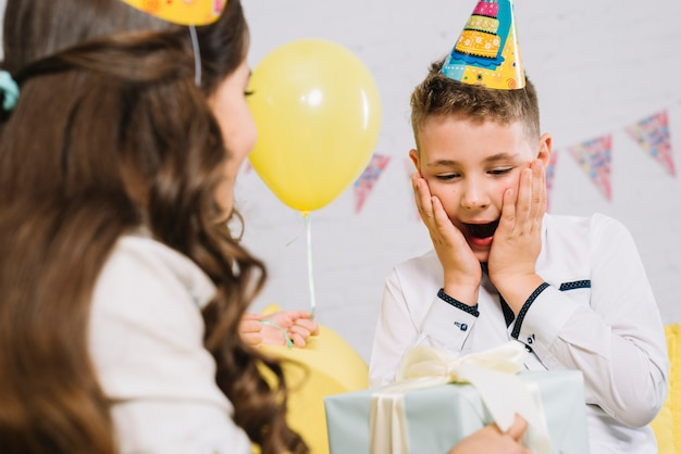 Portrait of a boy get surprised after receiving gift box from her friend