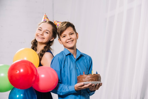 Portrait of a boy and girl holding colorful balloons and cake on plate