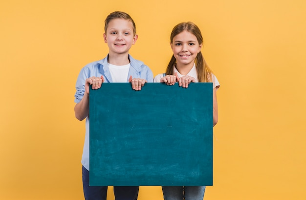 Portrait of boy and girl holding green chalkboard standing against yellow background