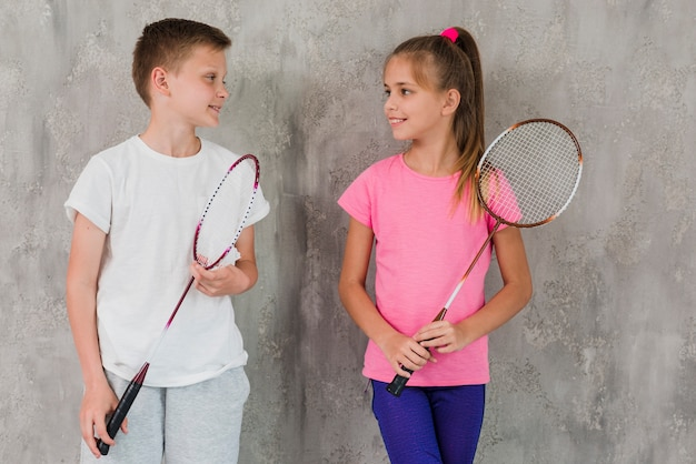 Portrait of a boy and girl holding racket in hand standing in front of concrete wall