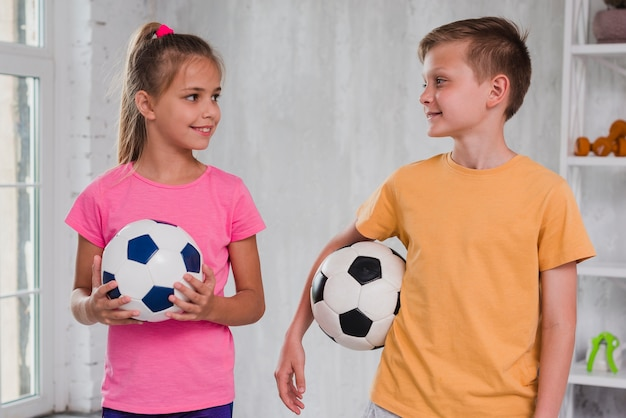 Portrait of a boy and girl holding soccer balls in hand looking at each other