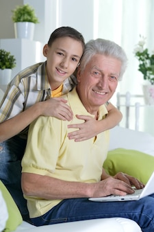 Portrait of  boy and  grandfather with a laptop at home
