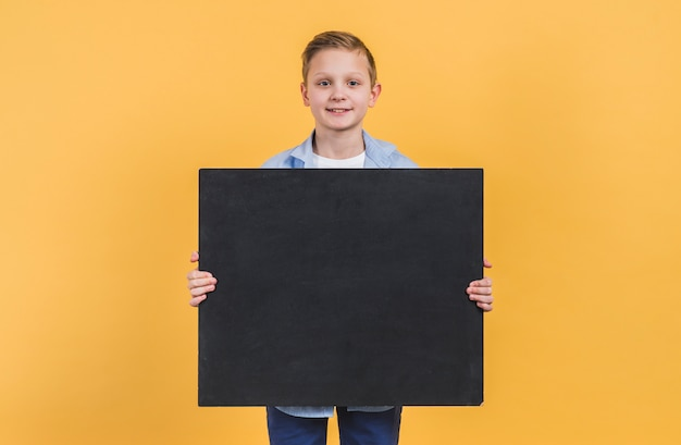 Portrait of a boy holding black chalkboard standing against yellow background