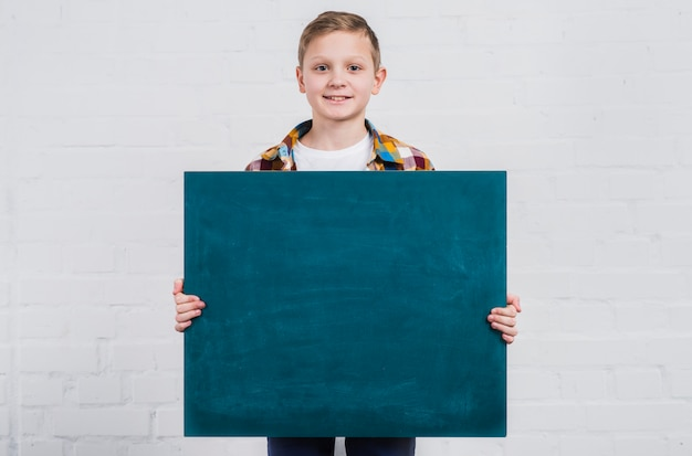 Portrait of a boy holding blank chalkboard standing against white brick wall