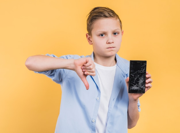 Portrait of a boy holding smartphone with cracked screen showing thumbs down against yellow background