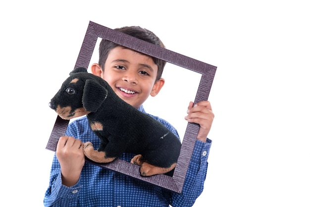 Portrait of a boy holding stuffed toy pet with frame on a white wall