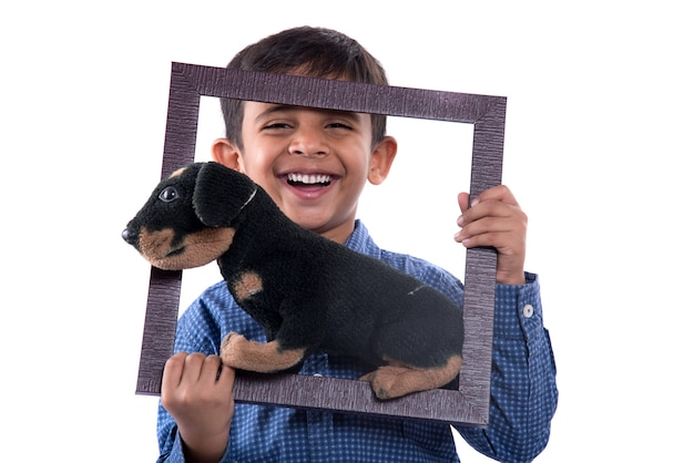 Portrait of a boy holding stuffed toy pet with frame