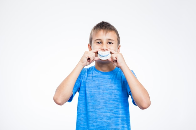 Portrait of a boy holding teeth plaster mold against white background