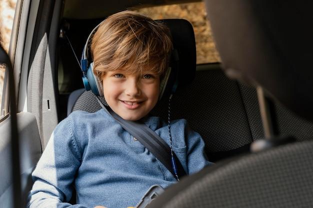 音楽を聞いているヘッドフォンと車の中で肖像画の少年